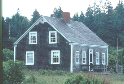 Early Cape Cod architecture style featuring 1.5 stories, extremely pitched roof, center chimney & clapboard siding